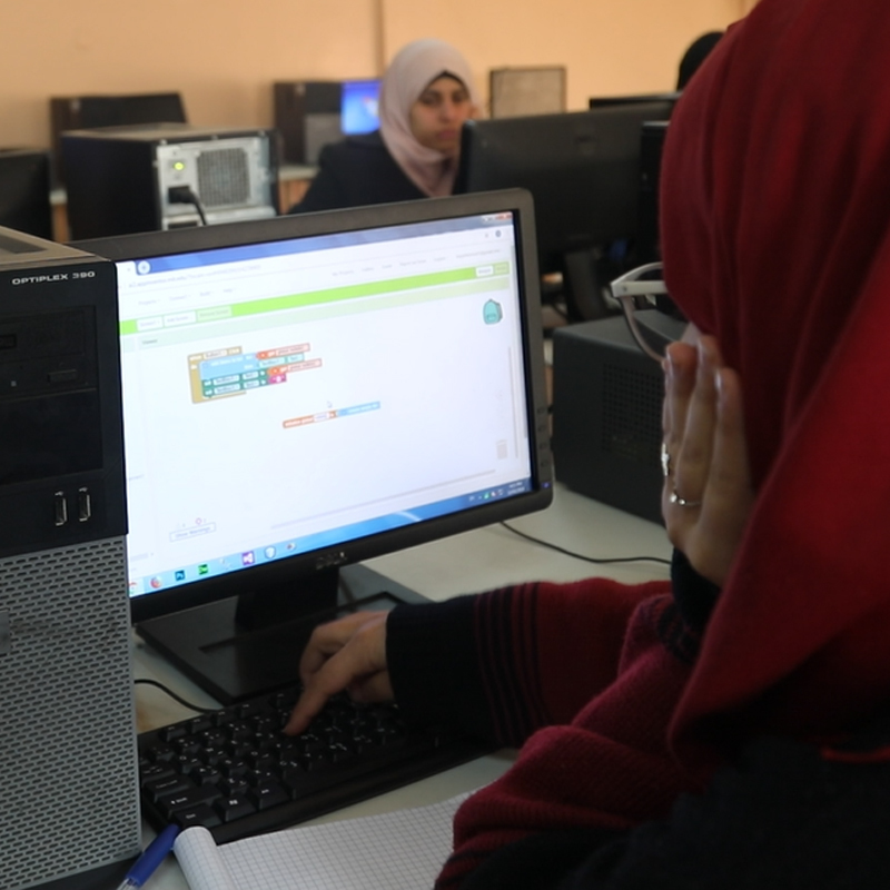 two girls work on app on their computer